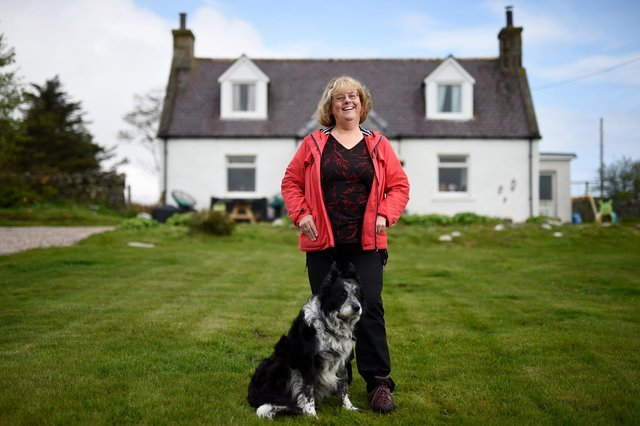 Wilma Robertson and her dog Bruiser stand in front of her croft.