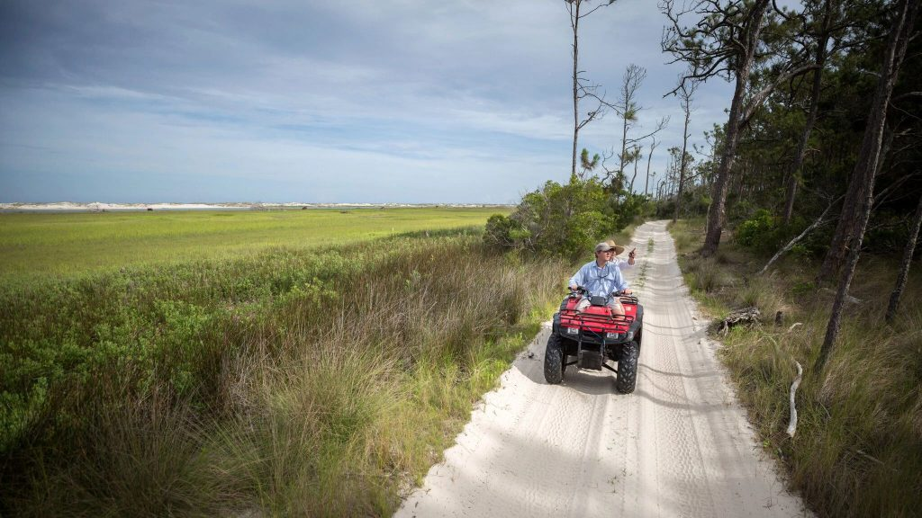 Little Cumberland Island property owners Kevin and Rebecca Lang drive a four wheeler along one of the island's few roads.Credit...Stephen B. Morton for The New York Times