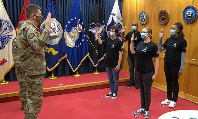 A picture containing person, floor, posing, group Description automatically generated Vice Chief of Space Operations General David Thompson swears in the first four enlisted recruits to the Space Force at Military Entrance Processing Station-Baltimore in Maryland on October 20, 2020. [Source: defensenews.com]