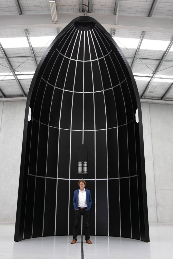 Rocket Lab founder Peter Beck with a mockup of the nose cone for his company's much larger, crew-capable Neutron rocket, due to be launched in 2024. Photo / Supplied